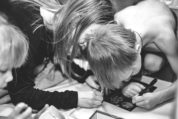 Children draw on paper on the floor