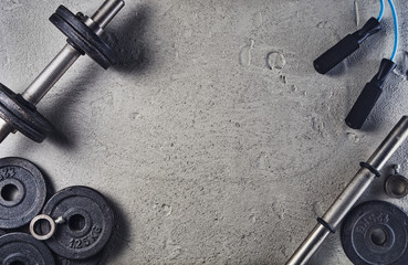 Photo on textile frame Fitness Fitness or bodybuilding concept background. Product photograph of old iron dumbbells on grey, conrete floor in the gym. Photograph taken from above, top view with lots of copy space