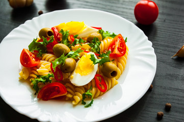 fusilli pasta salad with tomato, eggs and olive in plate on dark wooden background