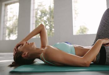 Smiling female lying on exercise mat at gym