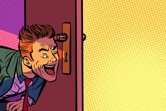 Businessman spying through the keyhole