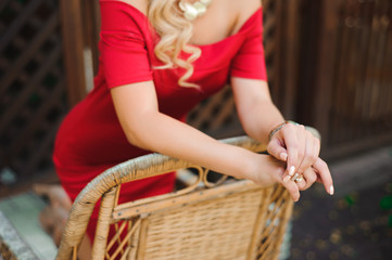 Portrait of young beautiful tanned blonde woman in red evening dress sitting outdoor in street cafe alone.