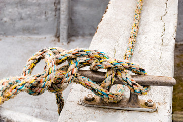 Boat moored in the harbor by a sailor's knot
