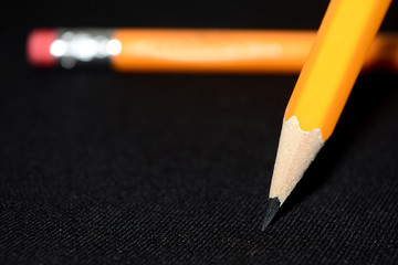 Two yellow Pencils on dark black blurred background. stationery. Office tool. Business concept. Back to school. Draw. Space for text.