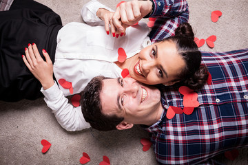 Happy man and white looking at camera while lying on the floor with small red hearts arround