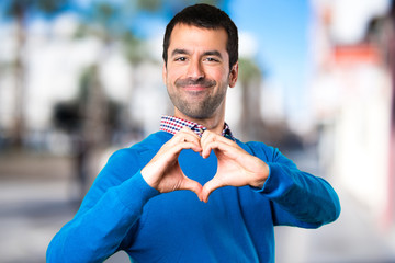 Handsome young man making a heart with his hands on unfocused background