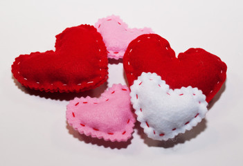 Five handmade cloth hearts, two larger red ones, two smaller pink ones and a smaller white one on a white background
