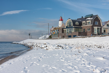 Winter landscape with Dutch beach covered with snow and view at lighthouse of fishing village Urk