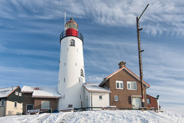 Dutch winter with snow and view at lighthouse of fishing village Urk