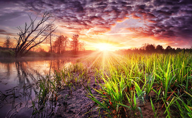 Spring landscape of colorful sunrise with beautiful sky over river. Wild spring nature in the morning. Vivid sunbeams on horizon and shining green grass on shore.