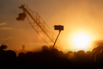 Smartphone on self-stick vs Television Camera hanging on crane, sunset time