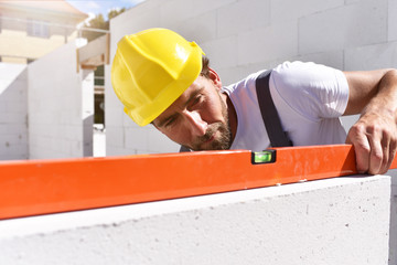 Maurer mit Wasserwaage kontrolliert Rohbau beim Bau eines Einfamilienhauses auf der Baustelle