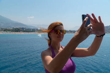 Attractive young girl taking a selfie portrait with cell phone on the boat, smiling.