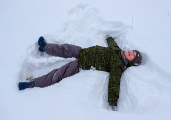 boy lying in the snow and waving arms and legs
