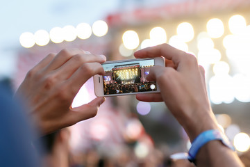 Man holding smartphones in hands and photographing. Taking photo on front stage on summer outdoor music concert festival