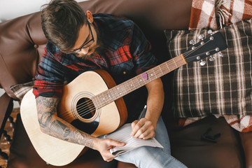 Young guitarist hipster at home with guitar sitting writing notes top view
