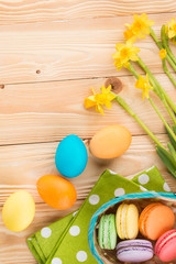 Happy Easter! Narcissus flowers on wooden background, colorful eggs, macaroons in basket, green napkin at white polka dots, top view.