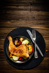 Barbecued chicken leg with baked potatoes and vegetables
