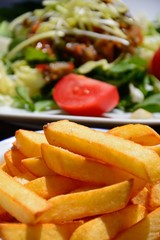 Crispy chunky chips with mixed salad topped with roast vegetables to the rear on a wooden table, Rabat, Gozo, Malta.