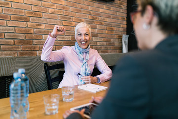Business meeting. Happy senior woman after successful job interview.