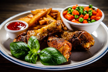 Grilled chicken legs with French fries and vegetables on wooden table background