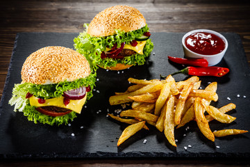 Two tasty cheeseburgers with french fries served on fashionable black desk