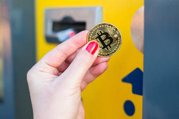 Woman pay with gold bitcoin at the vending machine. Close up.