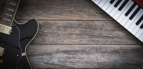 Black electric guitar and keyboard on a rustic wooden background