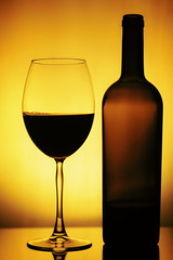 Glass and a Bottle of Wine. Bottle is open, half of it is Wine. Glass and Bottle of wine on a yellow background with a black vignette. Ellegant forms of Bottlr and Glass