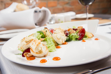 Starter: Mix salads, baked goat cheese, sea-buckthorn jam, caramelized pear with thyme, plum and roast nuts - served in a restaurant