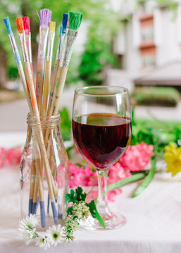 Glass of Red Wine with Paint Brushes and flowers