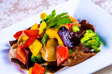 Vegetable stew with bell pepper, broccoli, celery and chinese mushroms in white plate