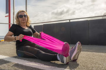 Mature woman (70-75) stretching with a stretch cord at open air public gym in Ipanema Beach, Rio de Janeiro, Brazil