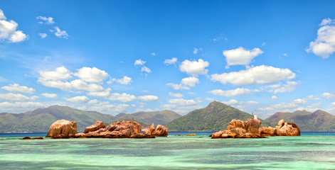Wall Mural - Granite rocks near La Digue coastline with Praslin Island in background, Seychelles
