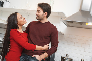 Young couple having romantic evening at home in the kitchen hugging