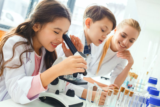 Little kids with teacher in school laboratory looking in microscope