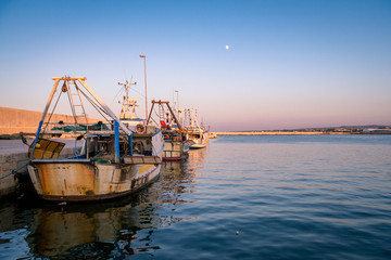 Sunset over trawler fishing boat docket in harbour. Apulia, Italy