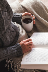 Woman wearing gray woolly cardigan enjoying a mug of tea and reading a book under a cozy blanket