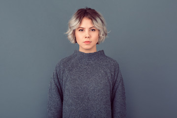Young woman in a grey sweater studio picture isolated on grey background serious