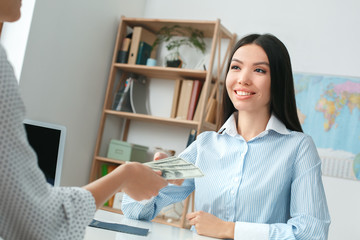 Young female travel agent consultant in tour agency with a customer cash payment