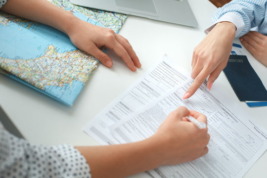 Young female travel agent consultant in tour agency with a customer signing documents