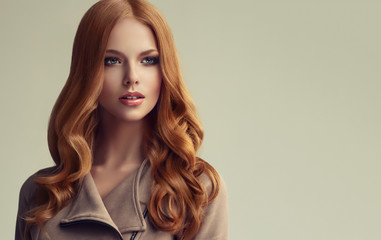 Red head  girl with long  and   shiny wavy hair .  Beautiful  model woman with curly hairstyle .