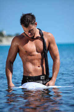 Muscular young sexy wet guy standing in the sea and takes off his business suit with a tie