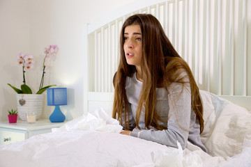 Young woman in bed sick holding many handkerchief