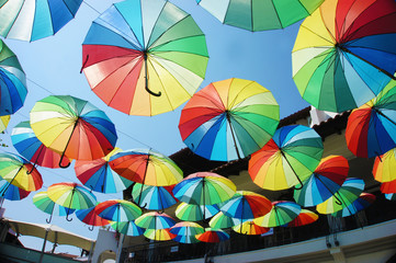 A lot of colorful umbrellas above the street