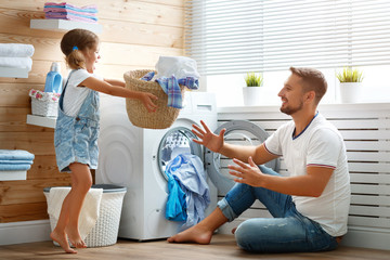 Happy family man father householder and child   in laundry with washing machine