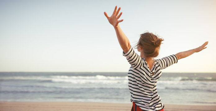 happy woman enjoying freedom with open hands on sea