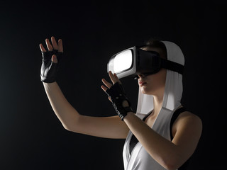 A girl in silver clothes with a hood and leather gloves in virtual reality glasses.