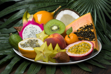 Exotic tropical fruits dish on palm leaves and wooden background, healthy food, diet nutrition, selective focus
