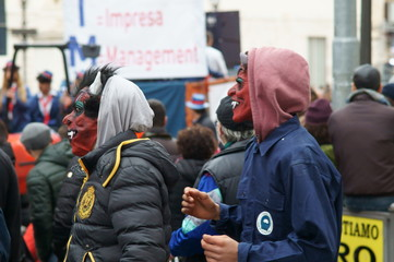 Carnival. People with traditional costumes, masks, and painted face.